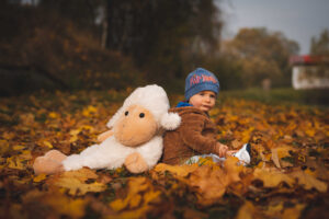 dítě s plyšákem v listí